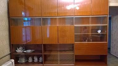 Витрина с деревянными шкафами для посуды в гостиной