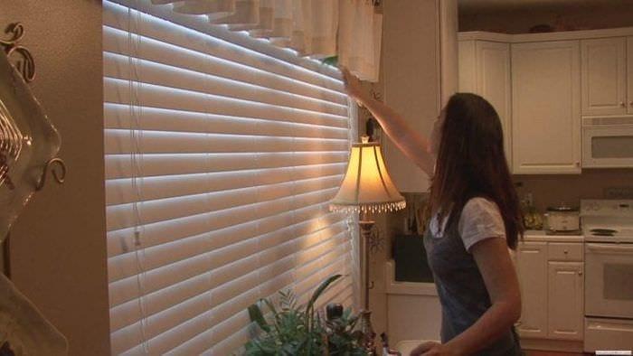 Белые жалюзи из обоев для широкого окна в гостиной