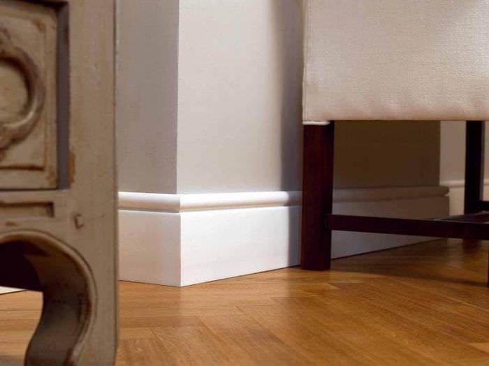 светлый плинтус из керамики в интерьере комнаты