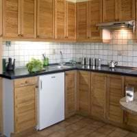 небольшой холодильник в фасаде кухни в белом цвете картинка