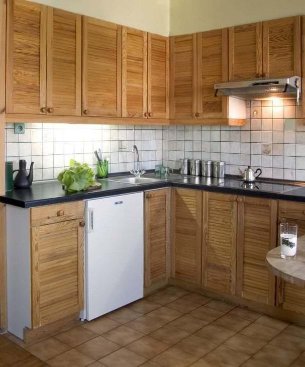 небольшой холодильник в декоре кухни в сером цвете