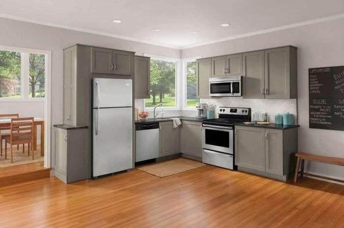 небольшой холодильник в фасаде кухни в темном цвете