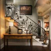 дизайн лестницы в доме с коваными перилами