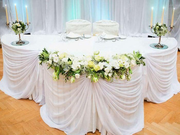 Свадебный стол с белой декорирующей тканью и подсвечниками