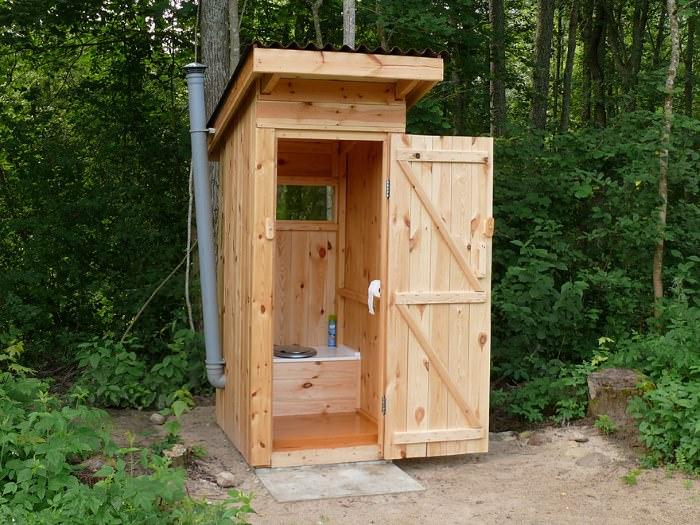 Уличный деревянный туалет с открытой дверью