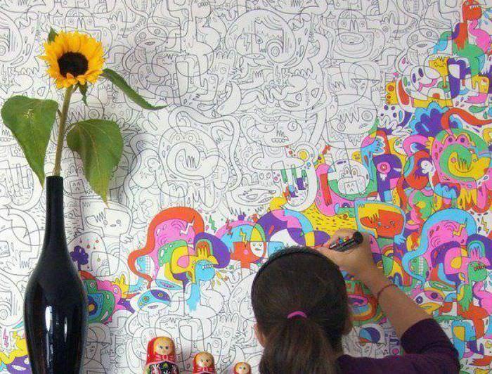 Девочка разрисовывает обои-раскраски в своей комнате