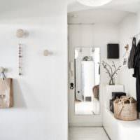 Зеркало и вешалка на стене современной прихожей
