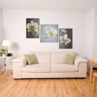 Картины с цветами на окрашенной стене гостиной