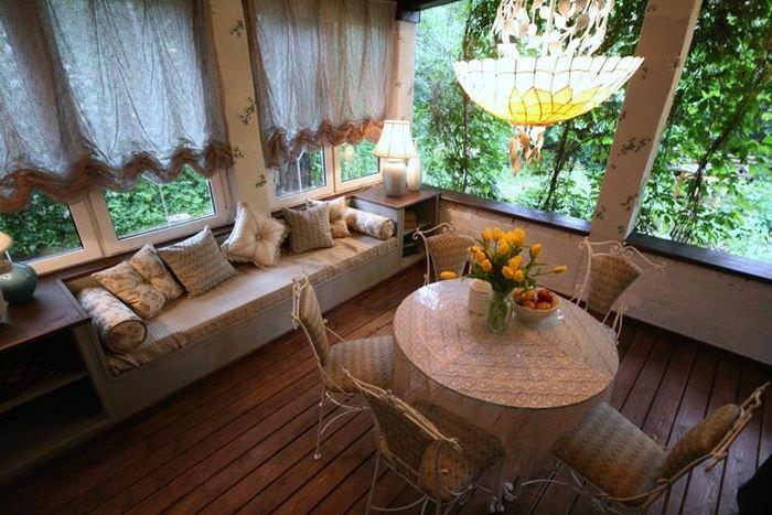 Обеденный столик и мягкий диван на веранде дачного домика