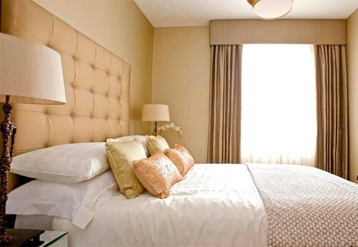 Выделение изголовья кровати контрастной отделкой стены в спальне 12 кв м