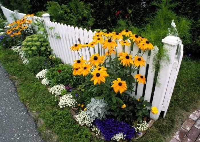 Белый деревянный забор в парадной зоне участка