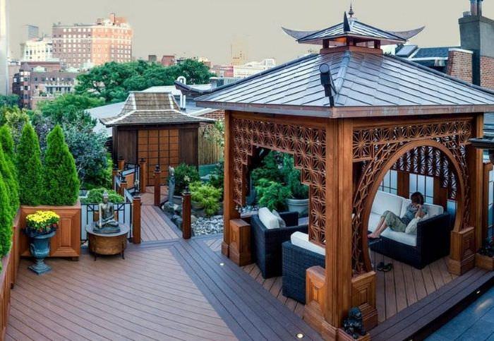 Беседка из дерева на крыше жилого дома
