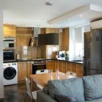 Темно-серый холодильник и мебель с отделкой под дерево в однокомнатной квартире