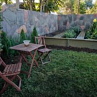 Складнын деревянные стулья и столик на зеленой лужайке