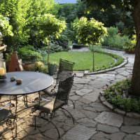 Кованная садовая мебель на площадке из песчаника