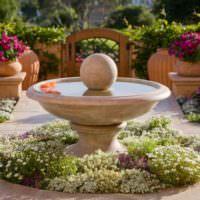 Декоративный фонтан в виде чаши в декоре сада