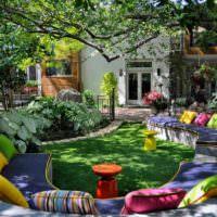 Яркие подушки на диванах под деревьями