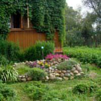 Небольшая альпийская горка перед террасой загородного дома