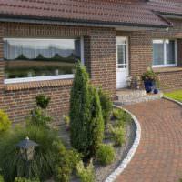 Клумба с хвойниками перед окном загородного дома