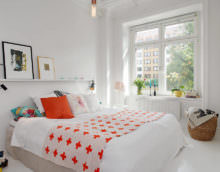Белая спальня и оранжевая подушка