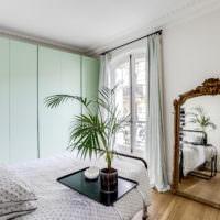 Шкафы мятного цвета и зекркало в спальне