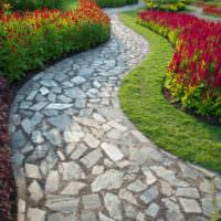 Дорожка из природного камня между цветущими клумбами