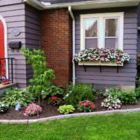 Клумба с цветами перед крыльцом частного дома