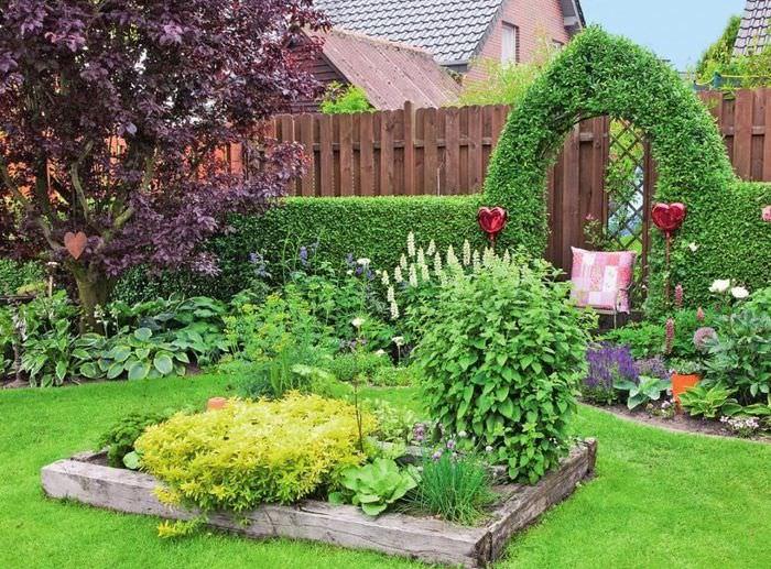 Деревянная клумба на газоне перед входом в сад