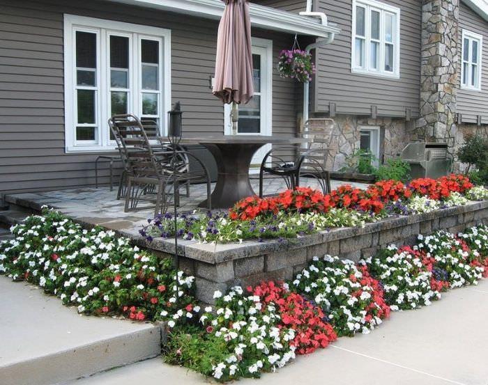 Цветущая клумба на открытой террасе загородного дома