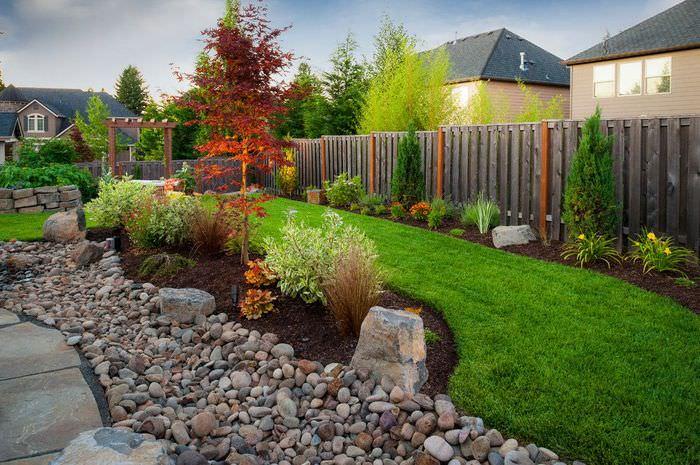 Узкая лента газона и природный камень в частном саду