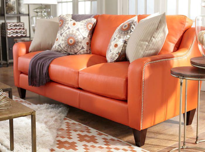 Кожаный диван оранжевого цвета в интерьере комнаты для гостей