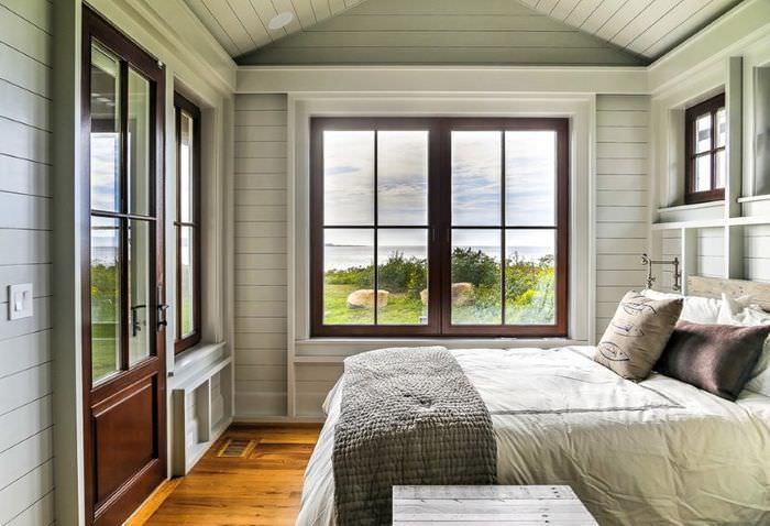 Интерьер спальни загородного дома с отделкой стен крашенной вагонкой