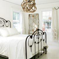 Черная кованная кровать в белой спальне