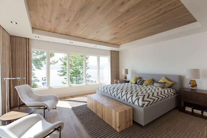 Интерьер спальни в духе минимализма с ламинатом на потолке
