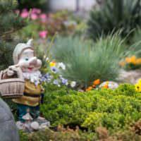 Сказочный гномик на клумбе садового участка