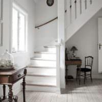 Белая лестница в прихожей жилого дома