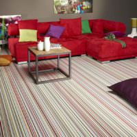 Красный диван на линолеуме в мелкую полоску