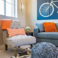 Оранжевый подушке в комнате с интерьером в пастельных тонах