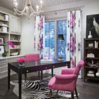 Кресло с розовой обивкой перед черным столиком