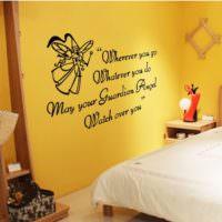 Надпись черным шрифтом на желтой стене спальни