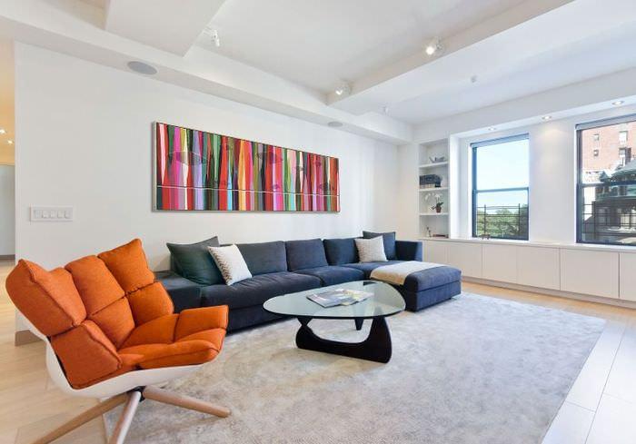 Дизайн белой гостиной с оранжевым креслом в интерьере
