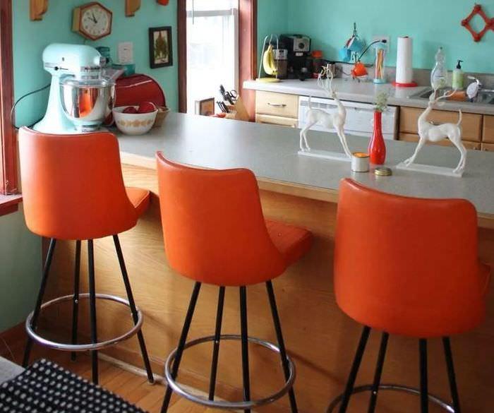 Оранжевые стулья вдоль барной стойки на кухне