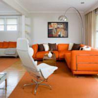 Интерьер гостиной с оранжевым диваном около окна