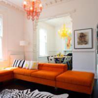 Мягкая мебель с оранжевыми подушками в интерьере гостиной