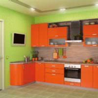 Зеленые стены и оранжевый гарнитур на кухне