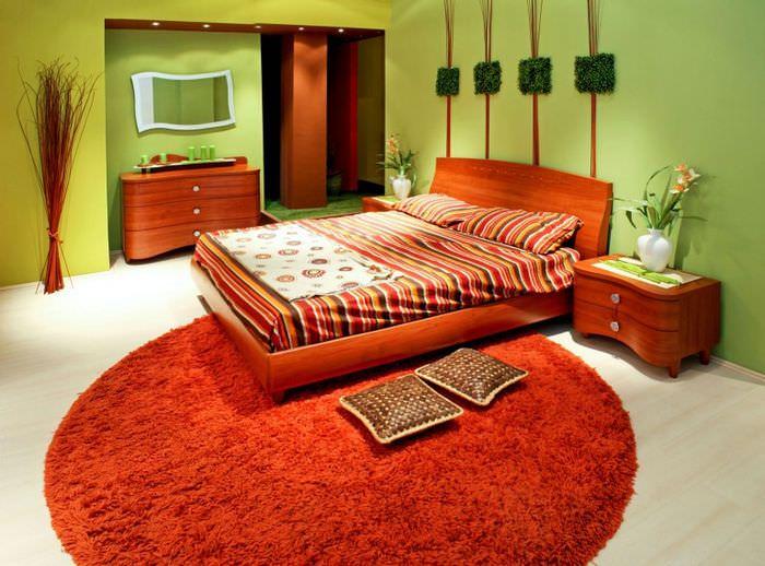 Оранжевые кровать и ковер в интерьере спальни