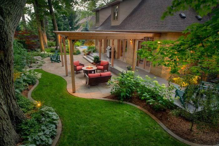 Место для отдыха под деревянной перголой рядом с дачным домом