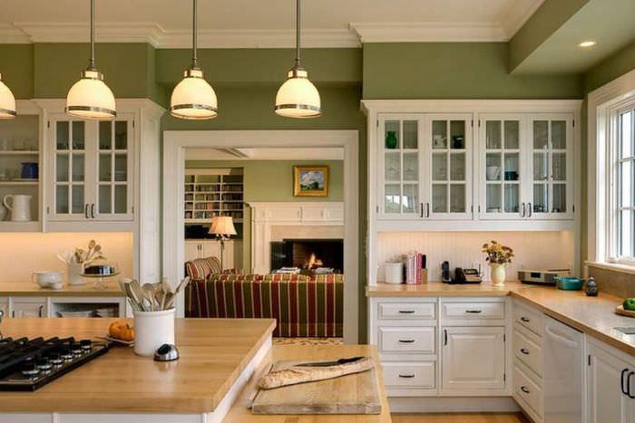 Интерьер кухни с белым гарнитуром и оливковыми стенами
