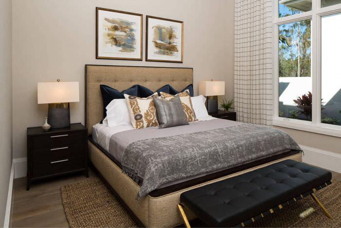 Красивая спальня с включенными светильниками на прикроватных тумбах