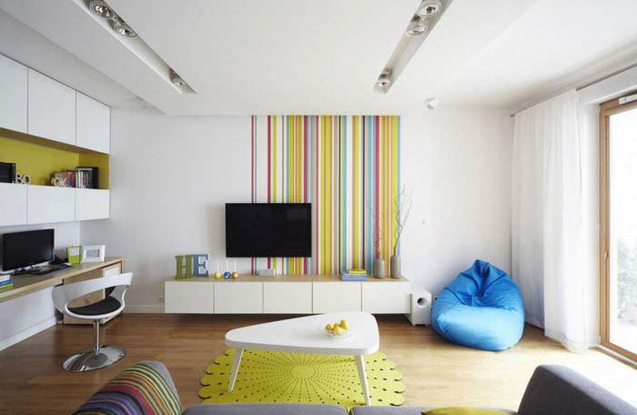 Обои с вертикальными полосками в интерьере гостиной с белыми стенами